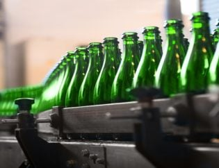 Green bottles on assembly line, coloured with iron chromite