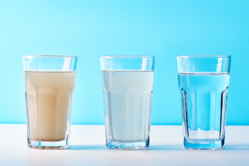 Water filters. Concept of three glasses on a white blue background. Household filtration system.