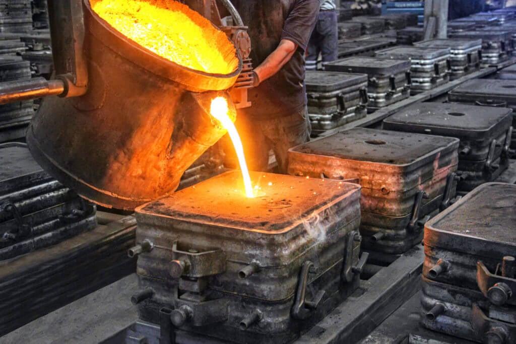 Mann gießt geschmolzenes Metall in eine Form